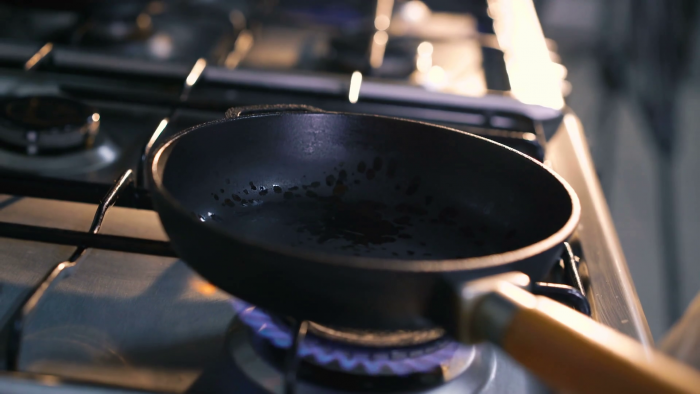Black pan with wooden handle of an open stove heating up.