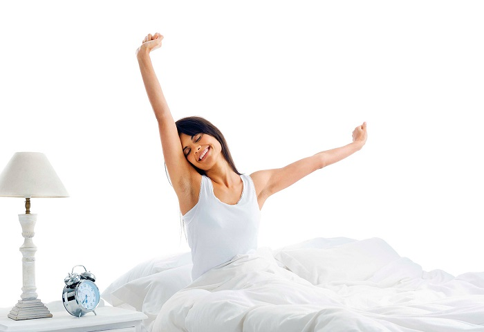 Women sitting up straight in a white bed to a white background, stretching and smiling. Table with a lamp and alarm clock to the left