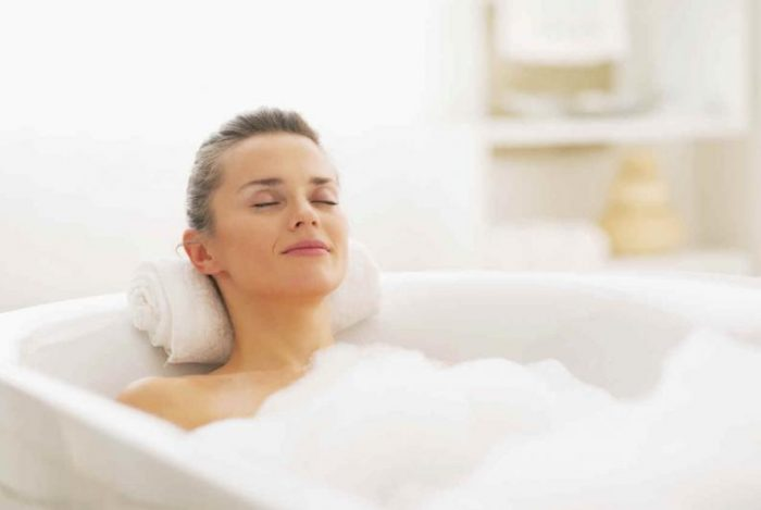 A smiling woman reclined in a white bathtub. She has her eyes closed and has a towel as a pillow