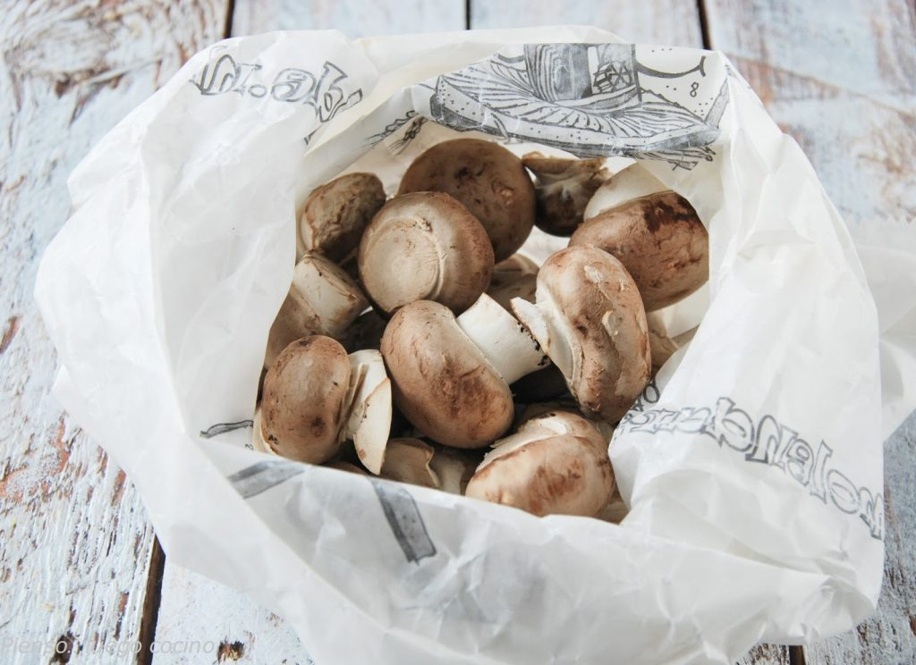 Open plastic bag full of fresh mushrooms, are in a container on top of a wooden table