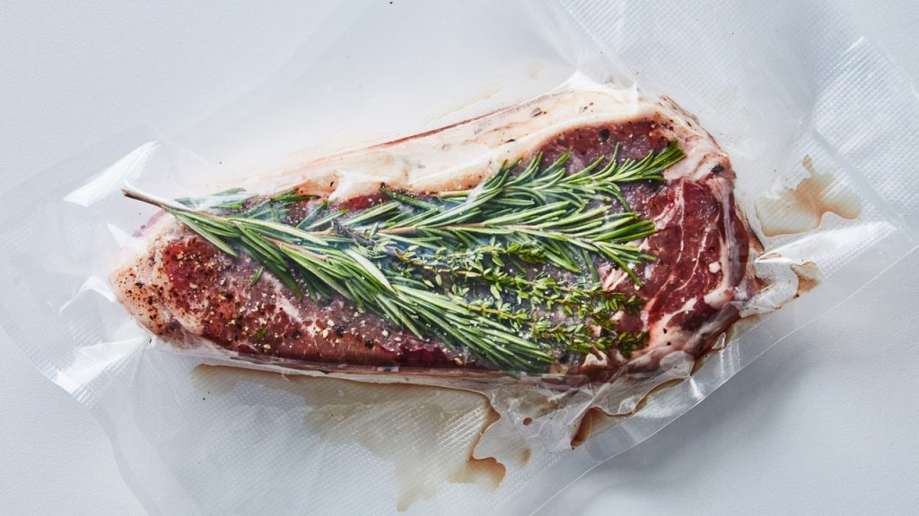 Fillet of meat inside a sealed bag of transparent plastic, a green branch is observed on top of the meat