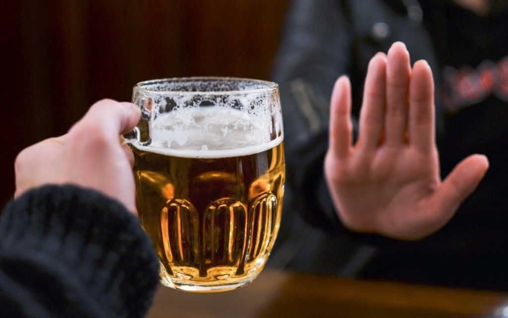 A beer mug and a hand of a man refusing to take it