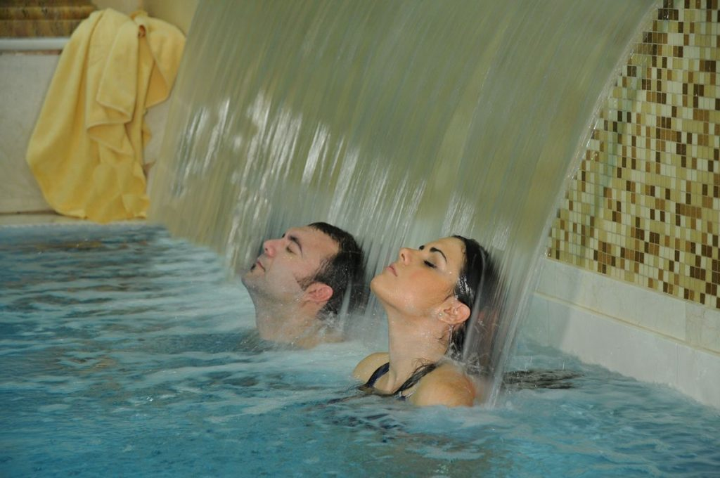 Man and Woman with closed eyes sitting with their heads back, inside a thermal pool. Both under an artificial water waterfall style sprinklers