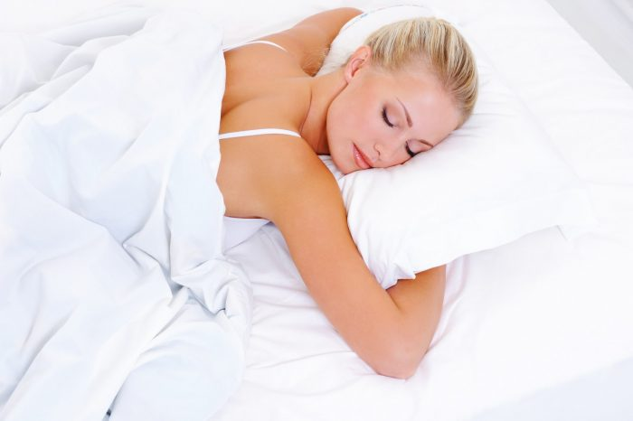 Woman with blonde hair sleeping upside down with her arms hugging her pillow. The all white lingerie