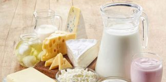 in a wooden table are different kinds of cheese, yogurt, milk and butter