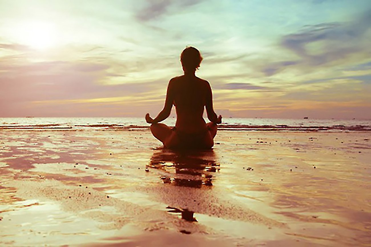 a woman meditating in the beach