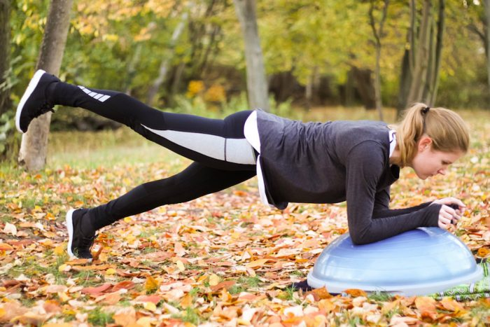Plank leg lift in a leafy park