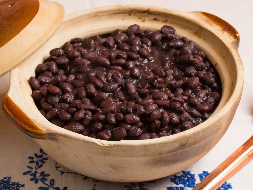 Round container of terracotta and lid, with black beans. Cover to one side, white tablecloth with blue flowers.