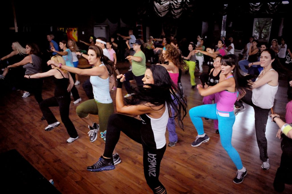 Many young women in sports lycra clothes of different colors, dancing to the same rite inside a dance hall, most with one leg raised