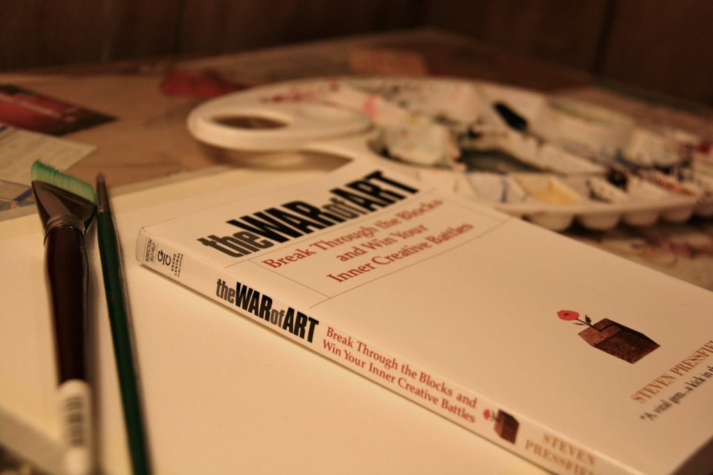 Cover of the book The War of Art author Steven Pressfield, white. Title in black and the rest of the letters in red. It is located diagonally on top of a table where implements are observed to paint in oil