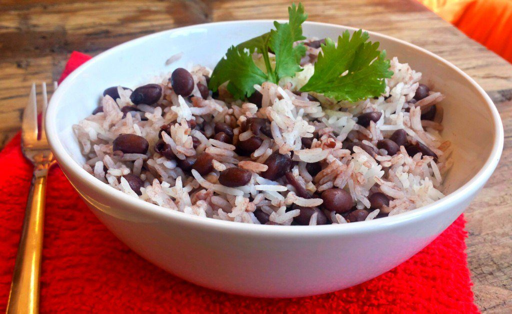 Plate with black beans attached with rice ready to eat. Red pepper and fork next to it