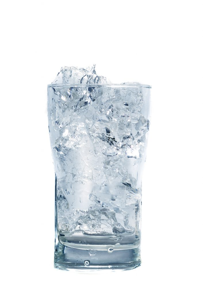 Transparent glass cup with many ice cubes