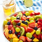 a bowl with pieces of different kind of fruits near is a jar with honey and a slice of a limon