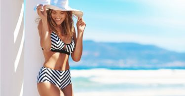 a woman near a beach wearing a black and white swimsuit and a hat