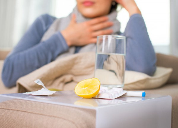 Woman sit in couch with sore throat