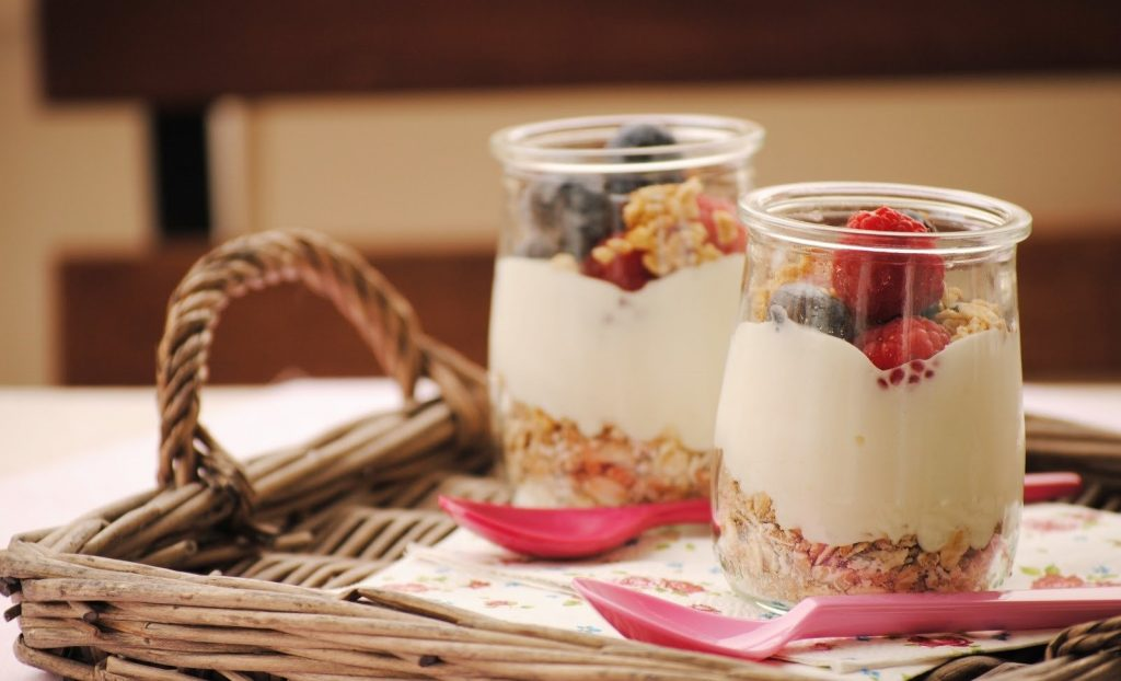 Two jars with cereal, strawberries and yogurt