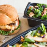 a burger and to containers with salad