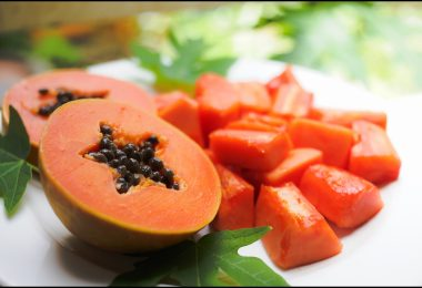 a papaya cut in half with some pieces around