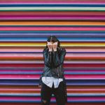 a woman in dark clothes covering her face in front of a colorful wall